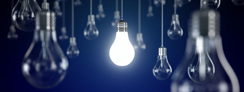 Hanging light bulbs with glowing one isolated on dark blue background