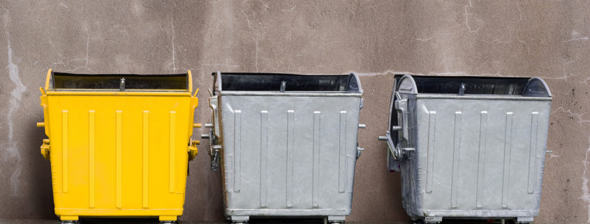 one yellow and two zinc garbage tanks near the wall