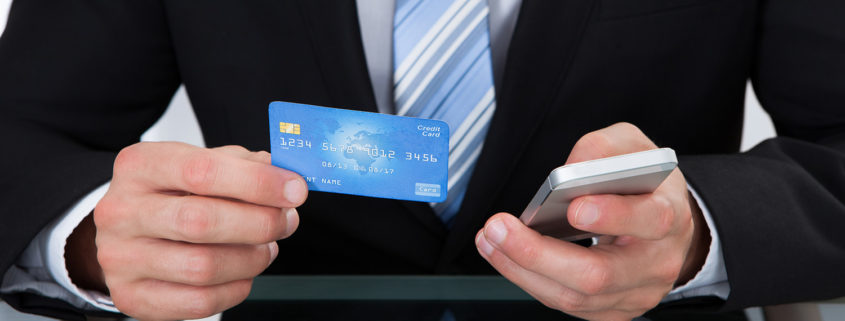 Businessman doing online banking or making a purchase through an online store using his dank credit card  and a mobile phone close up view of his hands